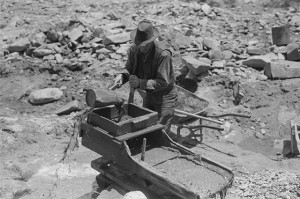 old prospector pouring water through his rocker box, Pinos Altos, New Mexico
