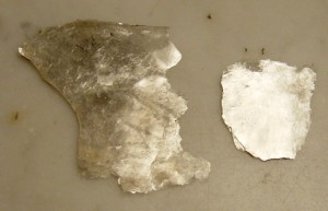 Flakes of the mineral Muscovite, a type of Mica. Mica occur in a variety of colors and composition. Muscovite is a common variety rich in Aluminium and Potassium.